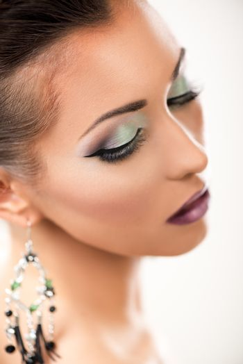Portrait of a attractive young woman with nice make up posing in a studio. Close-up.