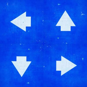 Four direction sign white arrows symbol on blue painted grunge metal background.