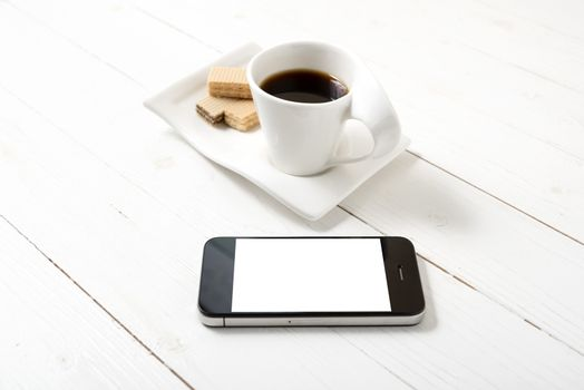 coffee cup with wafer and phone on white wood background