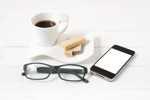 coffee cup with wafer,phone,eyeglasses on white wood background