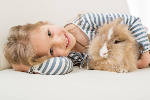 Little girl with her bunny laying on the sofa and hugging