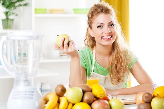 Beautiful young woman in a kitchen, holding an apple. Looking at camera.