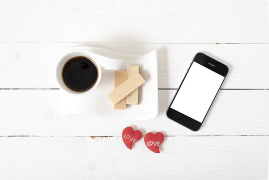 coffee cup with wafer,phone,heart on white wood background