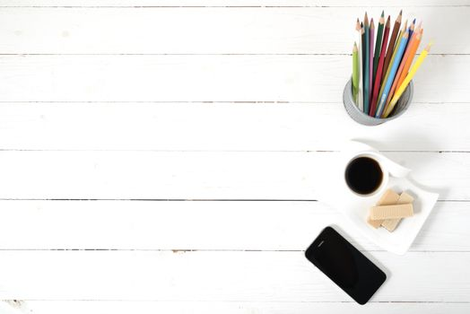 coffee cup with wafer,phone,pencil box on white wood background