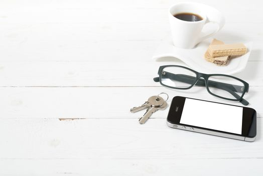 coffee cup with wafer,phone,key,eyeglasses on white wood background