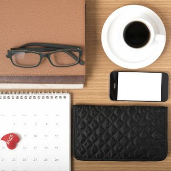office desk : coffee with phone,stack of book,eyeglasses,wallet,calendar,heart on wood background