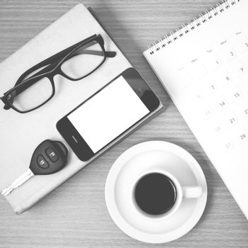 coffee and phone with car key,eyeglasses,stack of book,calendar on wood background black and white color