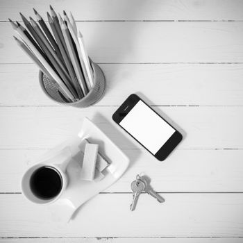 coffee cup with wafer,phone,pencil box,key on white wood background black and white color