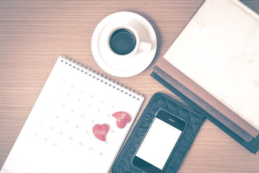 office desk : coffee with phone,wallet,calendar,heart,stack of book on wood background vintage style