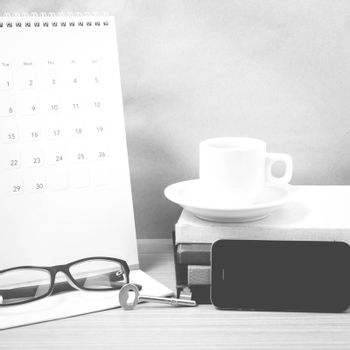 coffee and phone with key,eyeglasses,stack of book,calendar on wood background black and white color