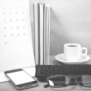 office desk : coffee with phone,stack of book,eyeglasses,wallet,calendar on wood background black and white color
