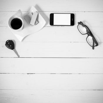 coffee cup with wafer,phone,car key,eyeglasses on white wood background black and white color