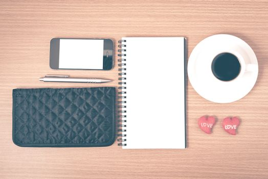 working table : coffee with phone,notepad,wallet and red heart on wood background vintage style