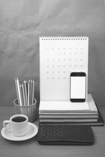 office desk : coffee with phone,wallet,calendar,color pencil box,stack of book on wood background black and white color