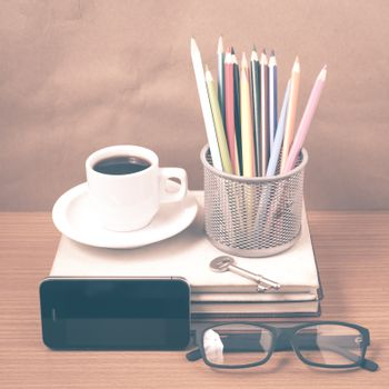 office desk : coffee and phone with key,eyeglasses,stack of book,pencil box vintage style