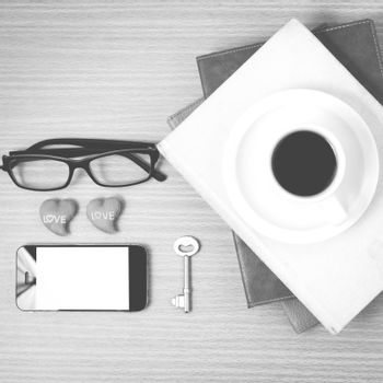 office desk : coffee and phone with key,eyeglasses,stack of book,heart on wood background black and white color