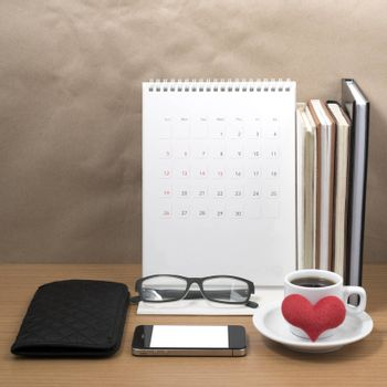 desktop : coffee with phone,stack of book,wallet,heart,eyeglasses,calendar on wood background