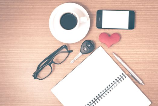 office desk : coffee and phone with car key,eyeglasses,notepad,heart on wood background vintage style