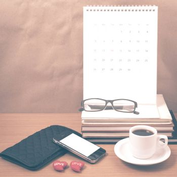 office desk : coffee with phone,wallet,calendar,heart,stack of book,eyeglasses on wood background vintage style