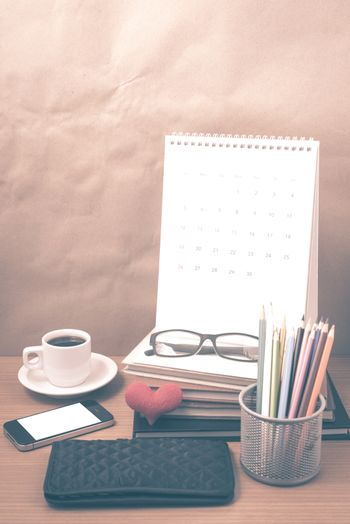 office desk : coffee with phone,wallet,calendar,color pencil box,stack of book,heart,eyeglasses on wood background vintage style