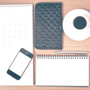 desktop : coffee with phone,notepad,wallet,calendar on wood background vintage style