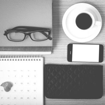 office desk : coffee with phone,stack of book,eyeglasses,wallet,calendar,heart on wood background black and white color