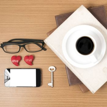 office desk : coffee and phone with key,eyeglasses,stack of book,heart on wood background