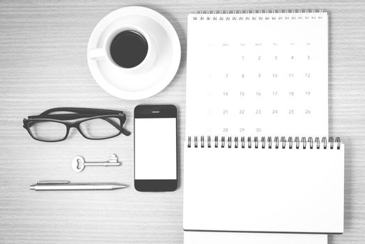 coffee and phone with key,eyeglasses,notepad,calendar on wood table background black and white color