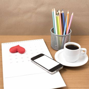 office desk : coffee with phone,calendar,heart on wood background