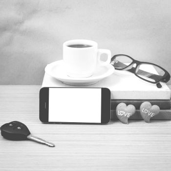 office desk : coffee and phone with car key,eyeglasses,stack of book,heart on wood background black and white color