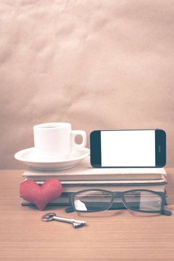 office desk : coffee and phone with key,eyeglasses,stack of book,heart on wood background vintage style
