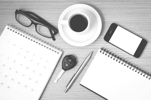 coffee and phone with car key,eyeglasses,notepad,calendar on wood background black and white color