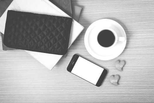 office desk : coffee with phone,stack of book,wallet on wood background black and white color