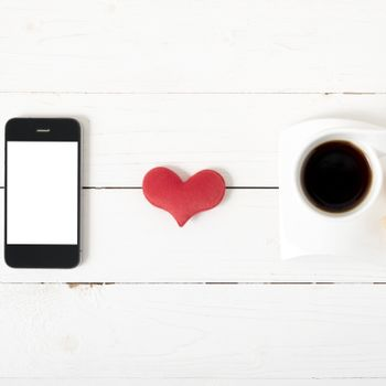 coffee cup with phone,heart on white wood background