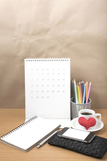 office desk : coffee with phone,wallet,calendar,heart,color pencil box,notepad,heart on wood background