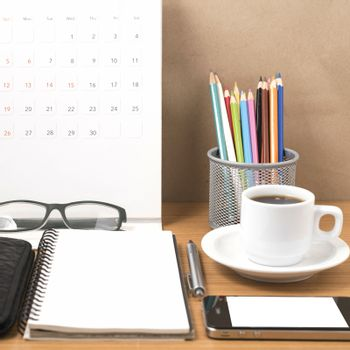office desk : coffee with phone,wallet,calendar,heart,notepad,eyeglasses,color pencil box on wood background