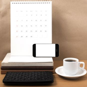 working table : coffee with phone,stack of book and wallet on wood background