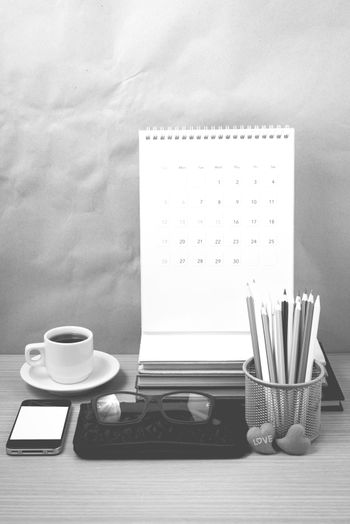 office desk : coffee with phone,wallet,calendar,color pencil box,stack of book,heart,eyeglasses on wood background black and white color