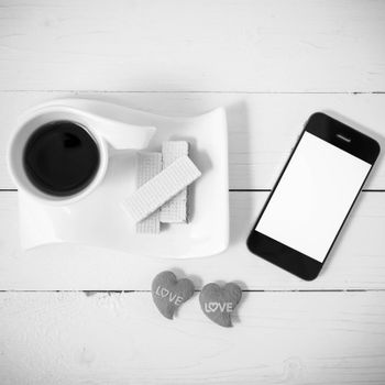 coffee cup with wafer,phone,heart on white wood background black and white color