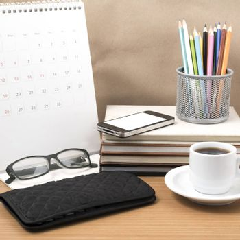 office desk : coffee with phone,wallet,calendar,color pencil box,stack of book,eyeglasses on wood background