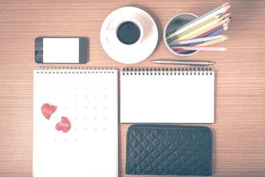 office desk : coffee with phone,wallet,calendar,heart,color pencil box,notepad on wood background vintage style