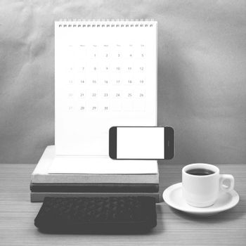 working table : coffee with phone,stack of book and wallet on wood background black and white color