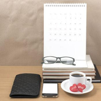 office desk : coffee with phone,wallet,calendar,heart,stack of book,eyeglasses on wood background
