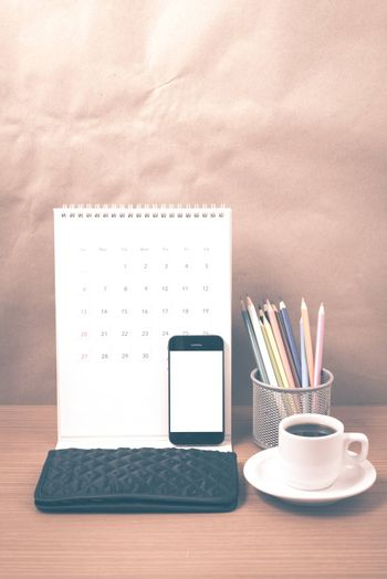 office desk : coffee with phone,calendar,wallet,color pencil on wood background vintage style