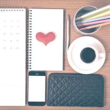 office desk : coffee with phone,wallet,calendar,heart,color pencil box,notepad,heart on wood background vintage style