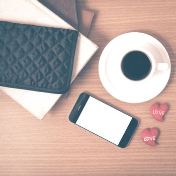 office desk : coffee with phone,stack of book,wallet on wood background vintage style