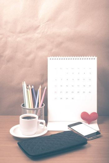 office desk : coffee with phone,wallet,calendar,heart,color pencil box on wood background vintage style