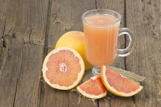 grapefruit juice and frish fruits on wooden background