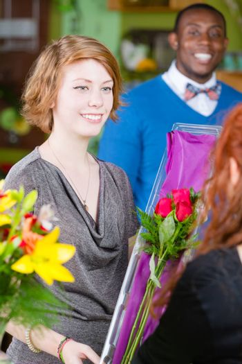 Teen girl purchasing roses at a florist shop