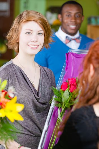 Smiling teenager purchasing roses at a florist shop